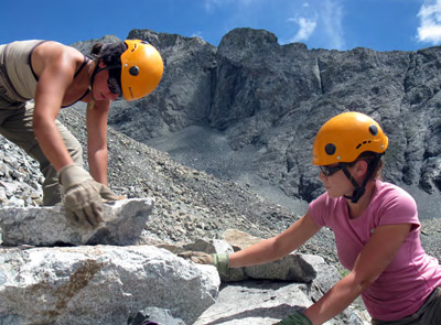 Photo of young women moving rocks on steep mountainside.