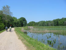 Bikers on dirt road next to a pond.