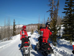Two crew members on snowmobiles.