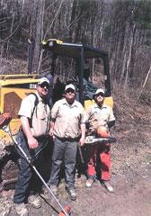 Three men holding trail restoration tools.
